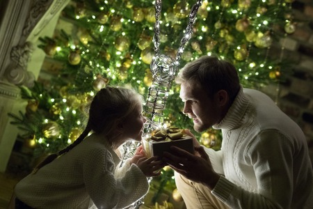 Father gives daughter a present near the Christmas tree.