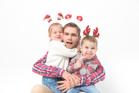 Father with children in funny christmas headbands on white background.
