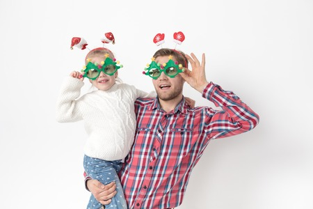 Father and daughter in funny Christmas accessories on a white background.
