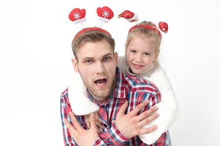 A little girl is sitting at her fathers back. Family in funny Christmas headbands on a white background. Stok Fotoğraf