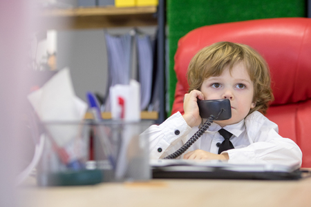 Little boy sits in the office in the chair and talking on the phone. Little boss.