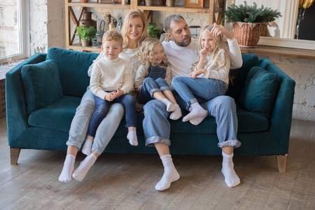 Happy parents and kids having fun tickling sitting together on sofa.