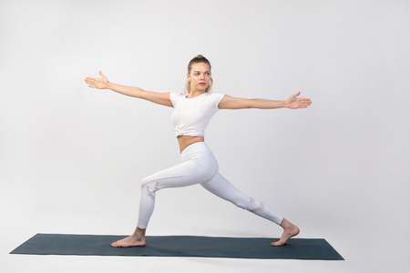 Sporty young woman doing yoga practice on white background. Stock Photo