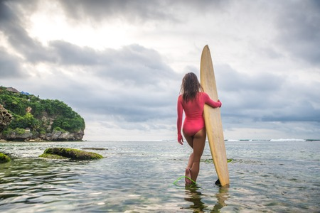 Beautiful woman in the pink swimsuit is standing in the ocean and holding a surfboard.