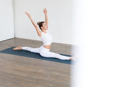 Sporty young woman doing yoga practice on white background at home.