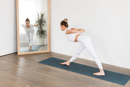 Sporty young woman doing yoga practice on white background at home. Reklamní fotografie - 116065520