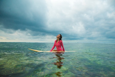 Beautiful woman swims on a surfboard. Stock Photo