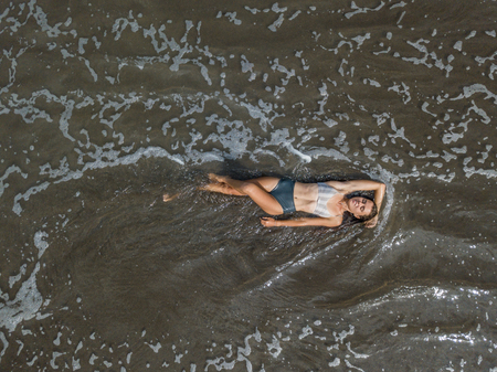 Top view of a woman lying on the beach with black sand, foaming waves of ocean.