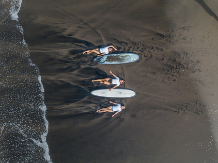 Top view of a women surfers with a board lying on the beach with black sand.