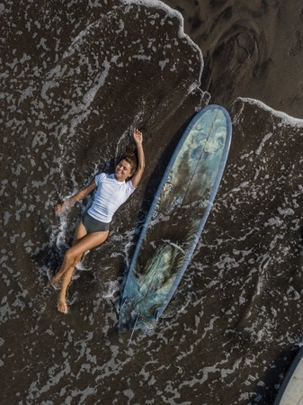 Top view of a woman surfer with a board lying on the beach with black sand.