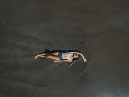 Top view of a woman lying on the beach with black sand.