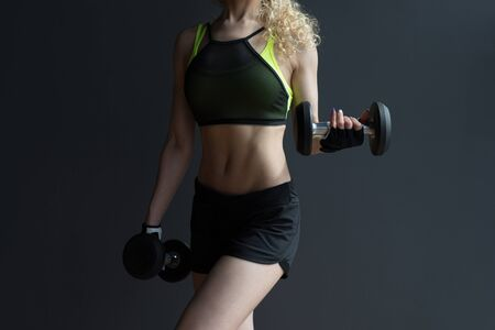 Athletic woman doing exercises with dumbbells in the gym.