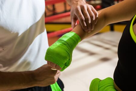 Sports man helps the girl to tie a boxing bandage. A man and a woman train in the boxing ring. Stock Photo