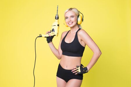 Young sexy woman in headphones holding a drill. Woman builder.