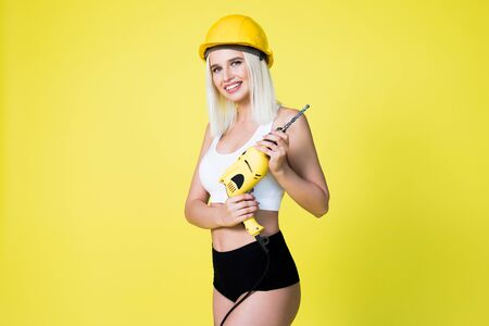 Young sexy woman in construction helmet holding a drill. on a yellow background Woman builder.