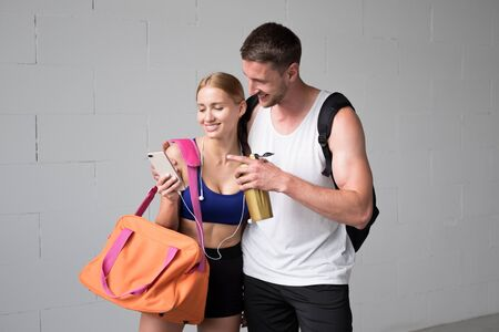 Sports couple going together to the gym and use a smartphone.