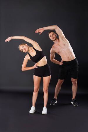 Athletic young couple doing stretching exercises together on the black background. Imagens