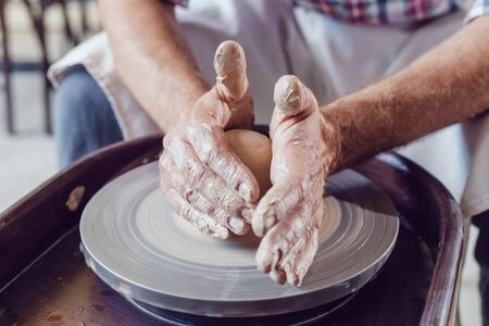 Man potter working on potters wheel making ceramic pot from clay in pottery workshop.