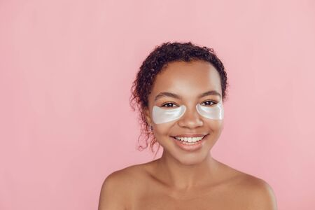 Young afro american woman with collagen pads under her eyes on pink background.