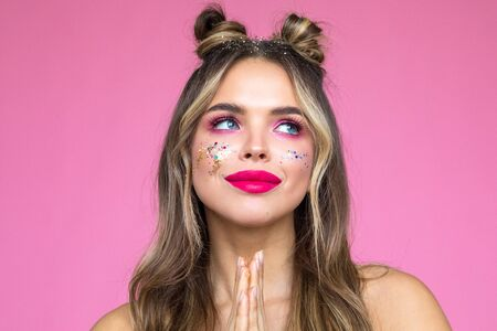 Girl with bright makeup on a pink background. Glitter Makeup.