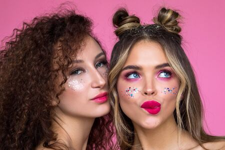 Beautiful and funny girls with bright makeup on a pink background.