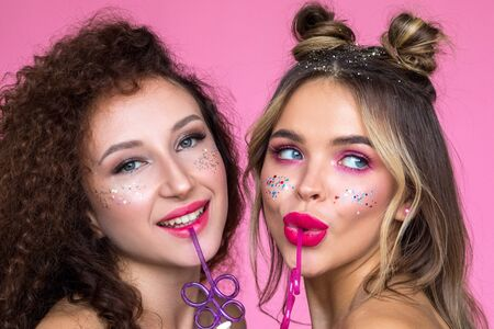 Girls with bright makeup on a pink background. Creative glitter makeup. Zdjęcie Seryjne