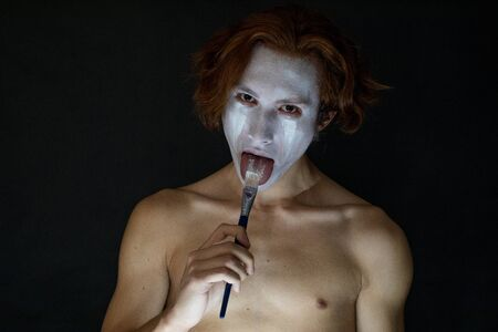A man applies makeup on his face and runs a brush over his tongue.
