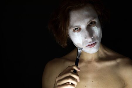 Man gets white paint on the face. Фото со стока