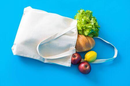 Bolsa ecológica de algodón con col rizada verde fresca y frutas sobre fondo azul. Compras ecológicas.