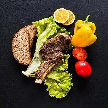 Ribeye Steak with fresh vegetables on dark background.