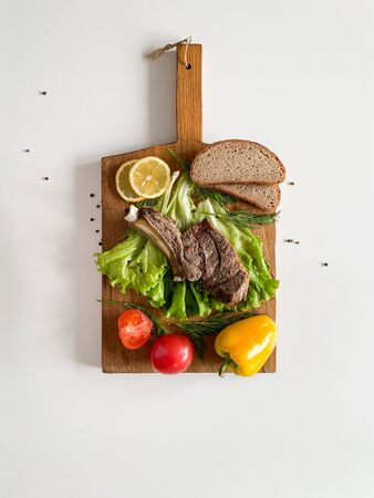 Ribeye Steak with fresh vegetables on a wooden board. Imagens