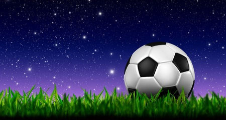 football in green grass over a twilight sky photo