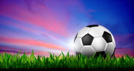 fútbol en pasto verde en el cielo de un crepúsculo Foto de archivo