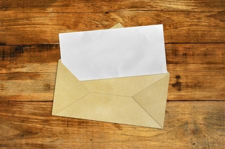 Vintage Envelope with blank paper on wood . photo