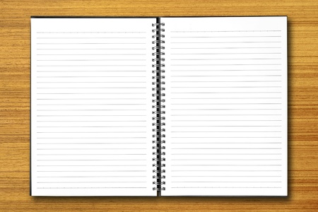 note book: White open notebook on wood background.