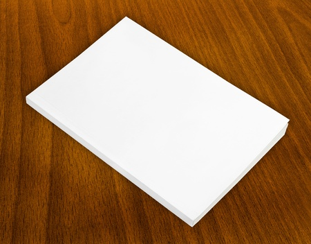 mag: Blank book with white cover on wood background.