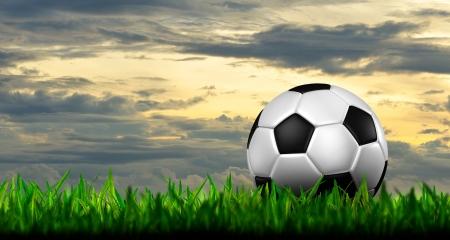 football in green grass over a twilight sky Stock Photo