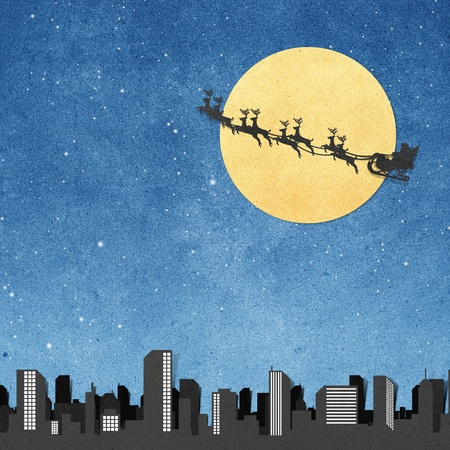 Santa Claus On Sledge With Deer And Moon above city panorama silhouettes  recycled papercraft photo