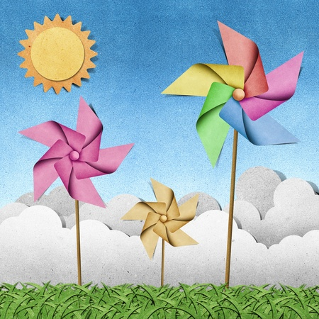 and craft materials: windmill on grass field recycled papercraft  background