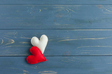 Valentines day concept. hand make two yarn red heart on wooden table and blue background