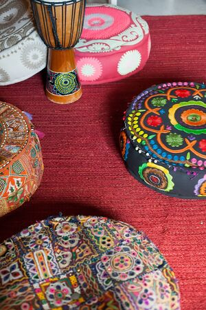 A Turkish traditional drum stands on the floor among bright bright puffs Zdjęcie Seryjne