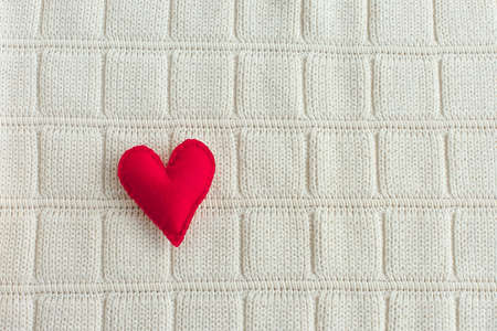 small red decorative felt heart on a soft background. Valentine's day