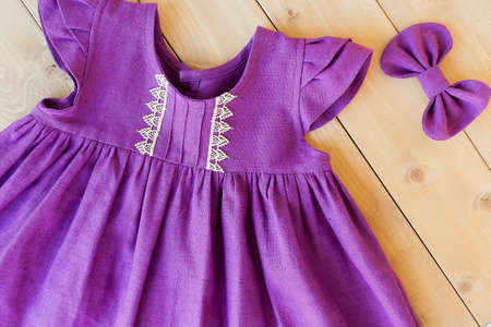 purple linen dress for a girl on a wooden background. children's clothes. fashionable dress