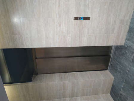 An empty modern elevator or lift with metal doors that are open in building with lighting
