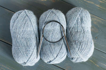 three balls of yarn and knitting needles on a wooden background, natural yarn. Handmade. Needlework.