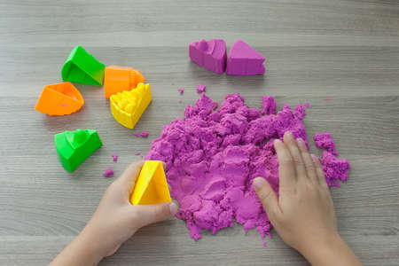 bright pink kinetic sand in the hands of a child. Development and education. Fine motor skills.