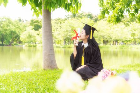 Beautiful asian women graduating holding diploma with pride and smiling in an academic gown.Congratulation happiness female student wearing graduation hat and gown ,background is nature in university.