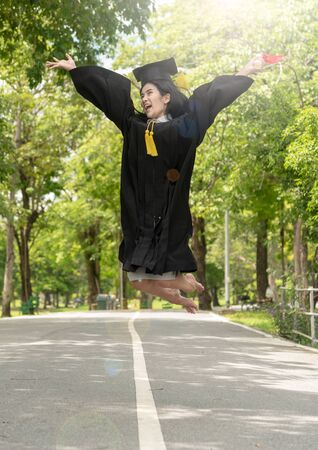 Happiness Young asian woman student in her graduation gown and wearing graduation cap with certificate in hands.Young female happy and jumping with Graduate day.Education finish congratulation concept 版權商用圖片