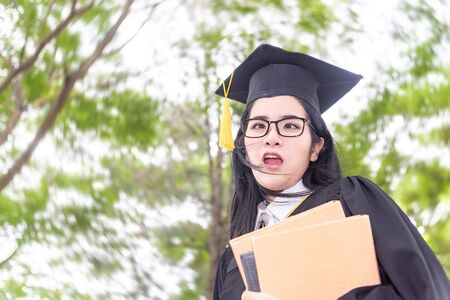 Young crazy asian woman graduating holding diploma with pride and funny in an academic gown.Congratulation happiness female student wearing graduation hat and gown ,background is nature in university. 版權商用圖片