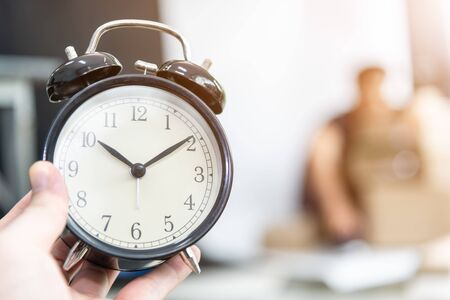Alarm clock in hand with worker man is working always on time at work .Time working and deadline business  concept
